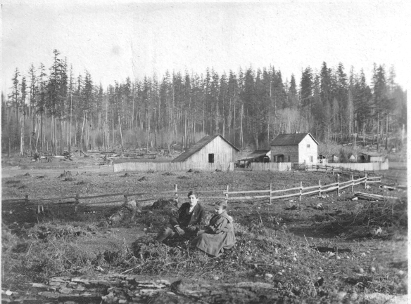"""A typical Western Washington Ranch. Home of C.B. Gates, Colby, Wash. Little daughter Bessie and her cousin Barstow Forbes in foreground.""  View is looking east toward hills of Banner district showing the Gates house, barn, and outbuildings."